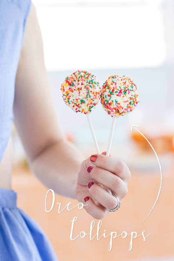 Girl holding two Oreo lollipops