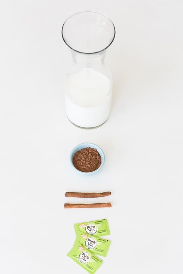 Almond milk, cinnamon, unsweetened coca powder, sugar free sweater on a table.