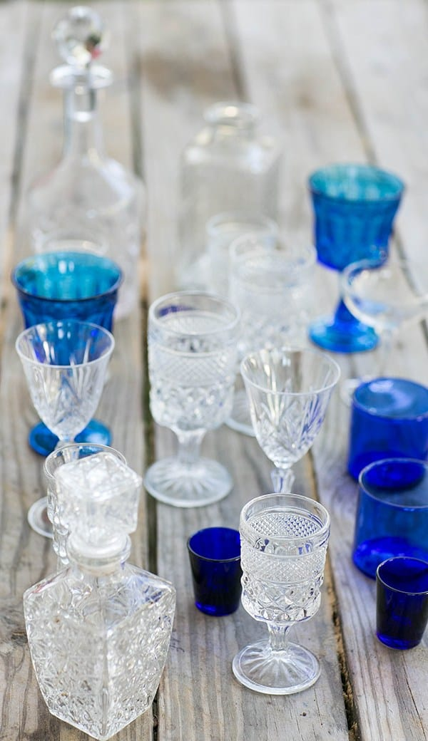 home bar ideas - Blue and white vintage glasses on a wooden table.