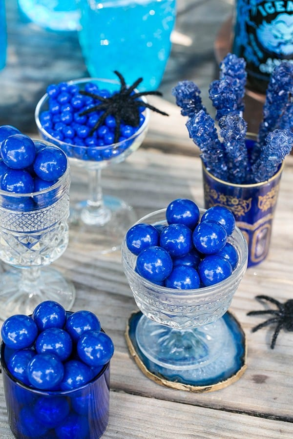 Round blue candy in glasses and blue rock candy.