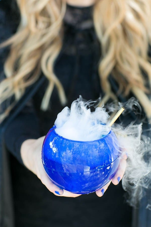 Eden Passante holding round blue glass with dry ice.