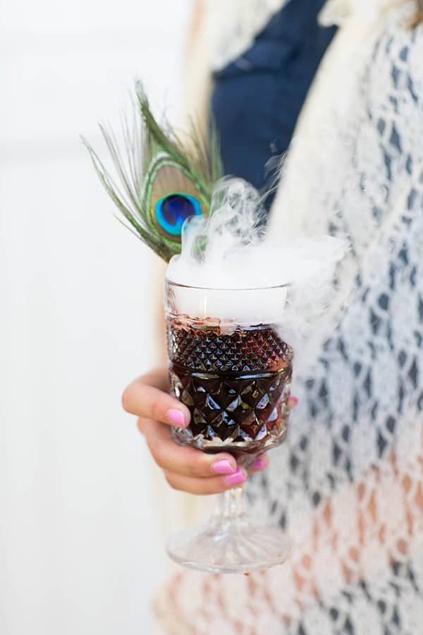 Lady holding cocktail with dry ice  and peacock feather.