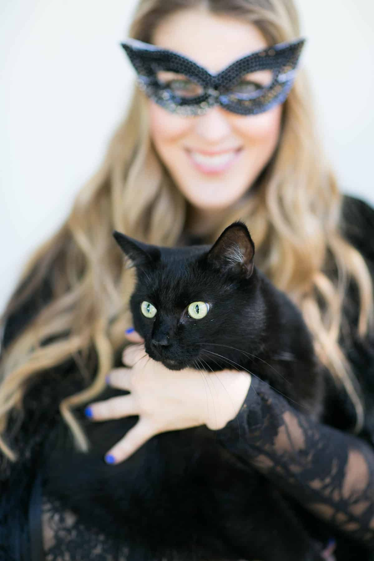 holding a black cat at a Halloween party