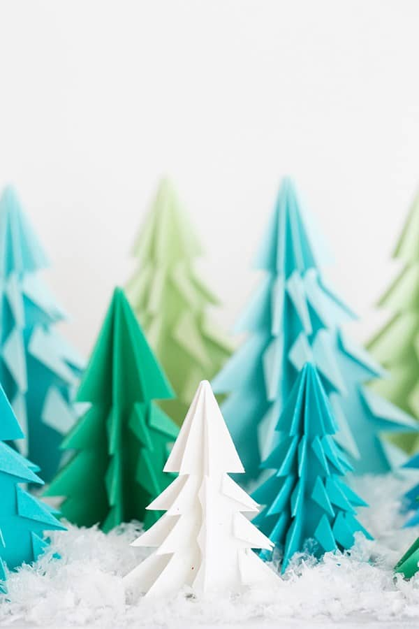 Paper origami trees on a table with fake snow.
