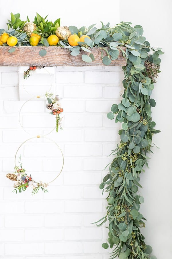 Garland on a mantle with orange and a modern wreath.