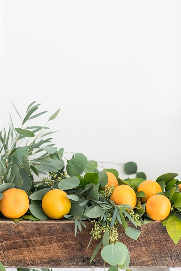 Green garland with oranges on a mantle.