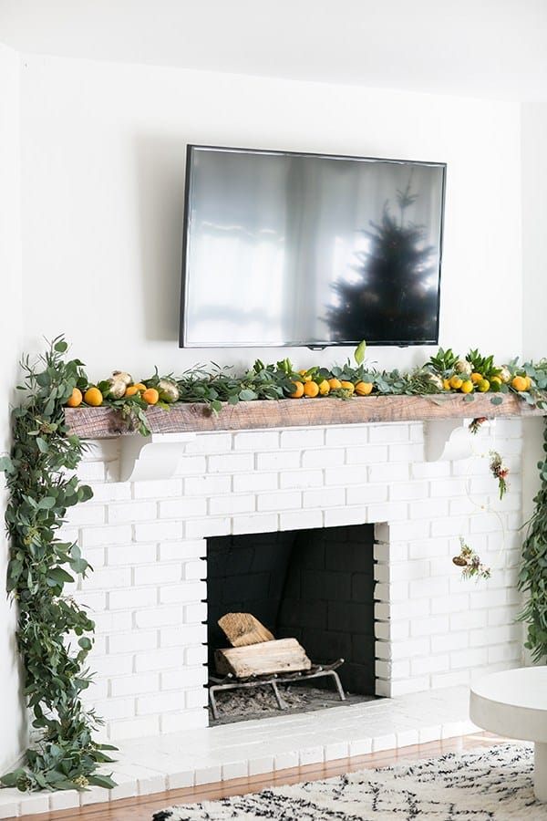 White fire place with TV above it and garland with oranges.