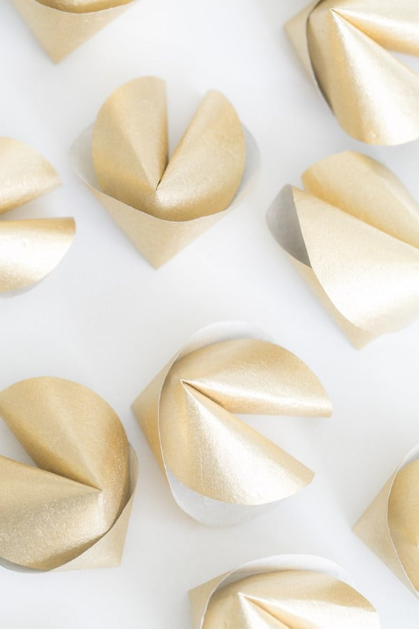 DIY gold paper fortune cookies on white table