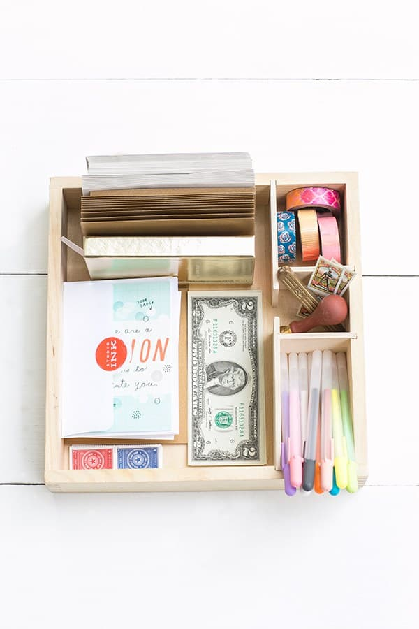 A wooden card box with money, cards, pens, tape and stamps.