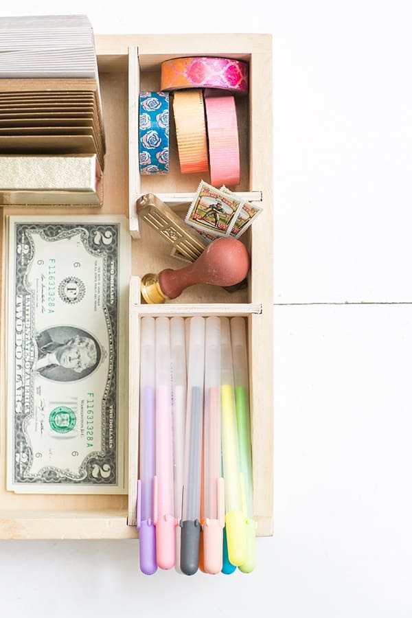 Colorful pens, money and cards in a card box.
