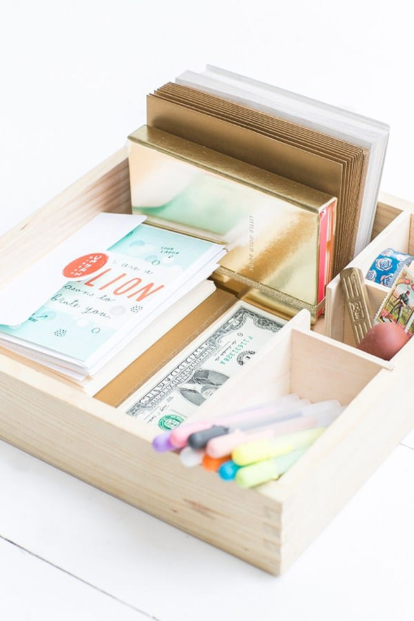 A wooden card box with cards, pens, envelopes and money.