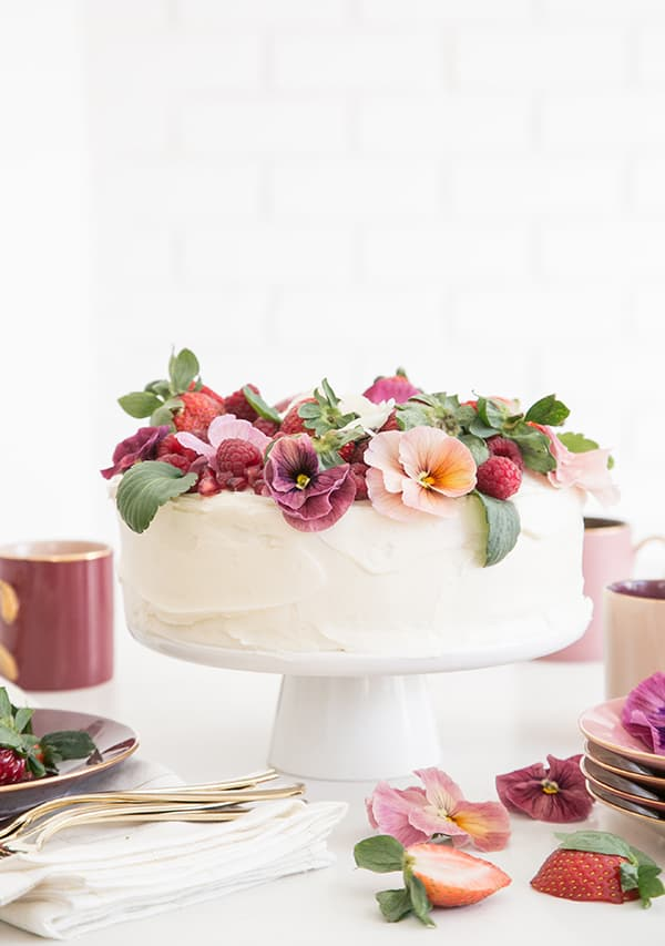 Side on shot of white cake with flowers and berries