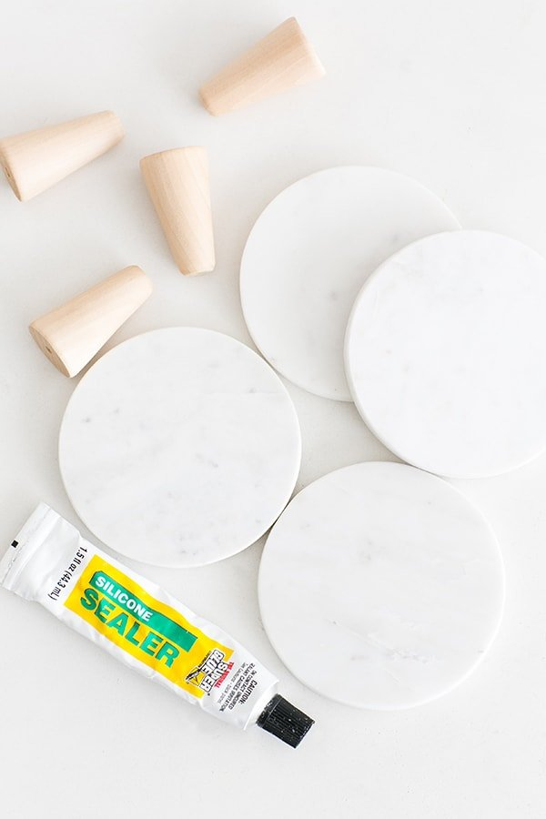 Marble coasters and wooden dowels and silicone sealer to make mini marble cake stands.