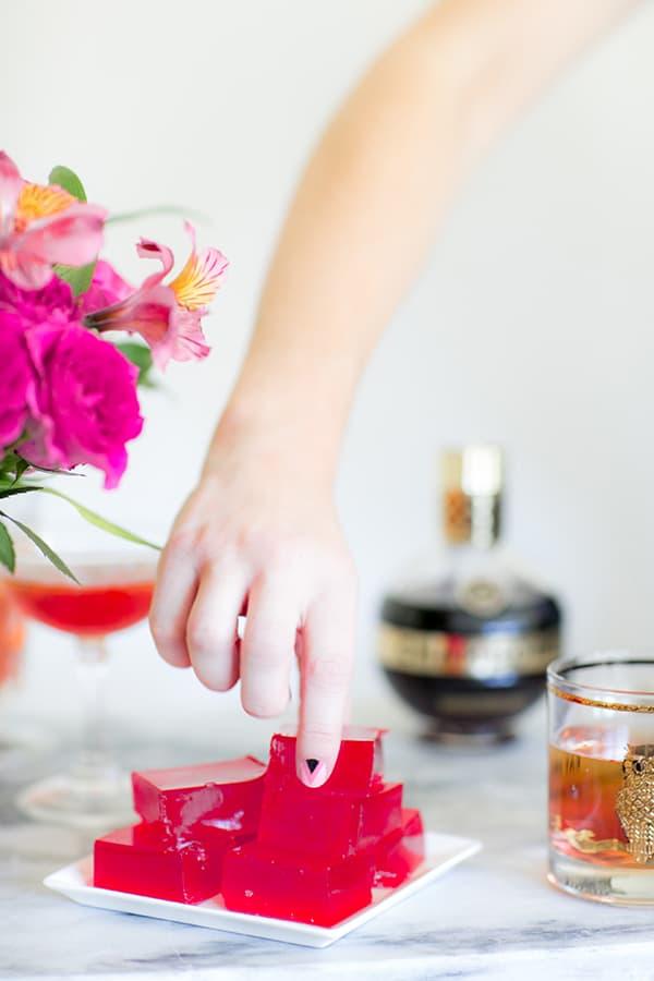Hand picking up a Chambord jello shot
