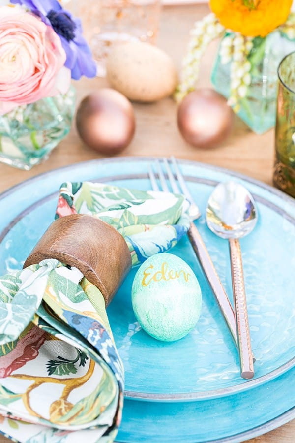 Colorful Easter brunch with blue plates, colorful napkins and copper silverware.
