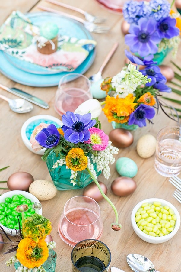 Colorful flowers in blue vases with copper Easter eggs
