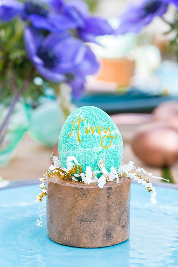 Green Easter egg with gold writing on a wooden stand.