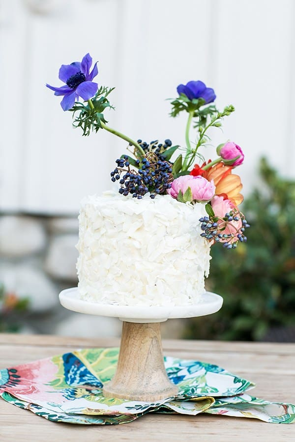 Carrot cake on a stand with flowers.