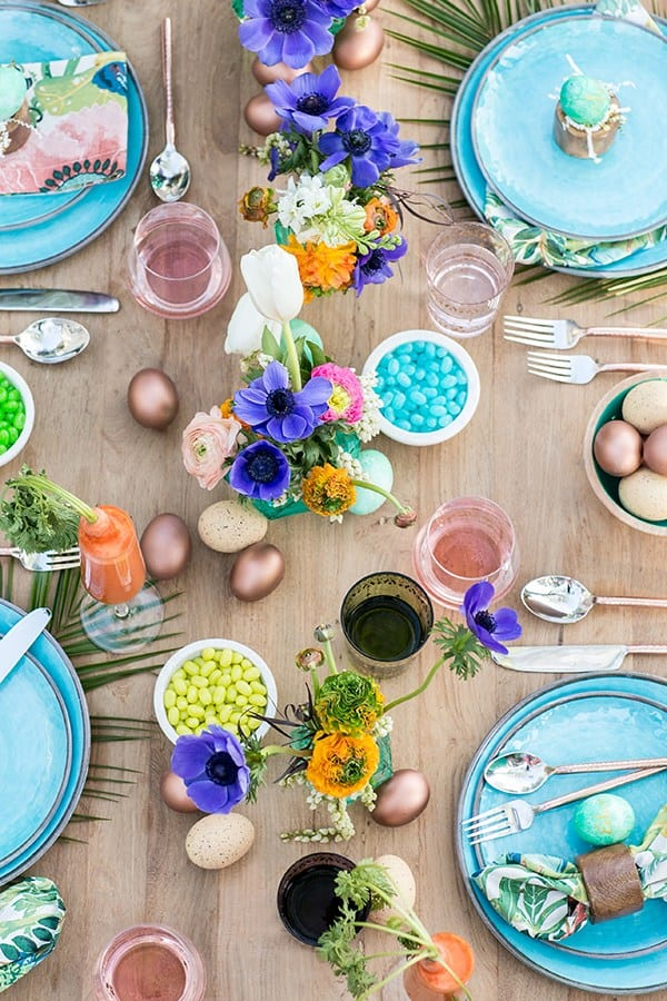 A colorful Easter brunch with flowers, jelly beans, blue plates and colorful eggs.