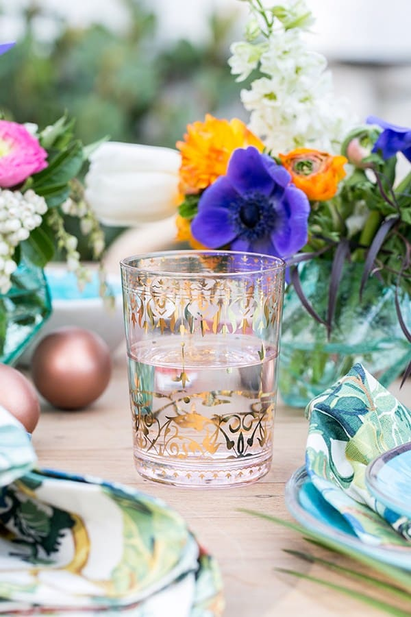 Pink glass with gold decorations and colorful Easter flowers.