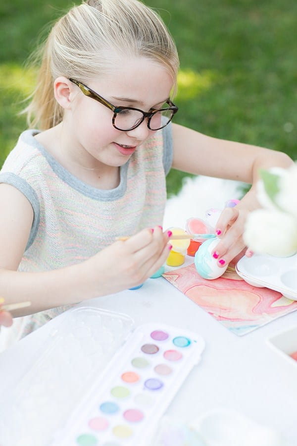 Girl painting an egg with watercolor