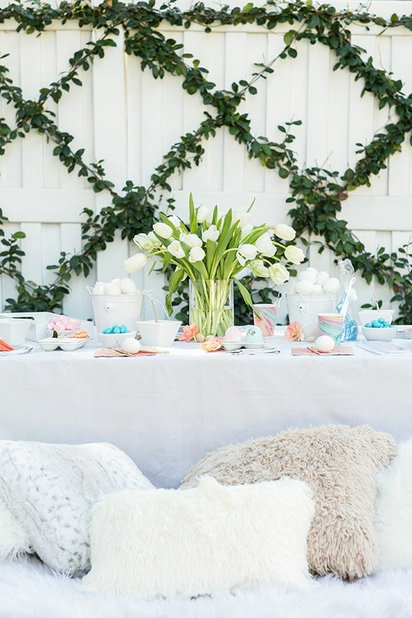 Easter party for kids with a table, flowers and throw pillows.