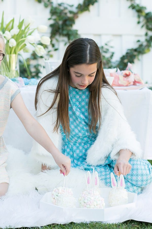 Two girls grabbing candy apples at an Easter party