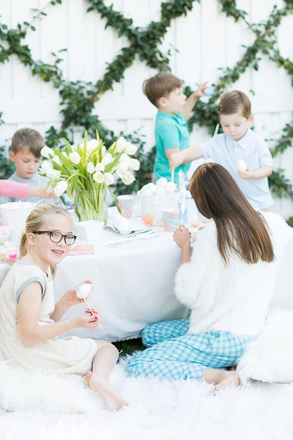 Kids sitting around a table at an Easter party decorating eggs
