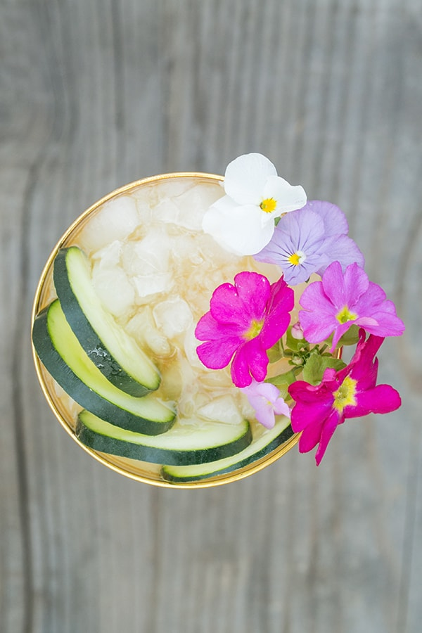 Overhead photo of a Pimm's Cup cocktail with edible flowers and cucumber slices.