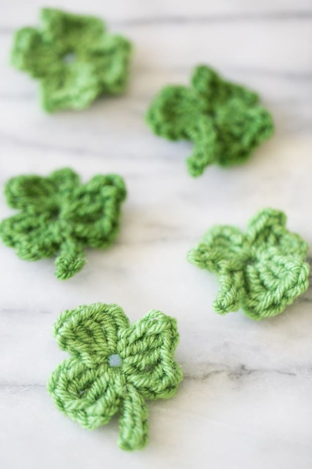 Mini crochet shamrocks on a marble table.