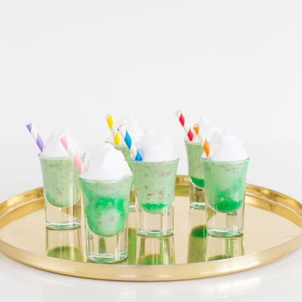 side shot of shot glasses filled with green liqueur