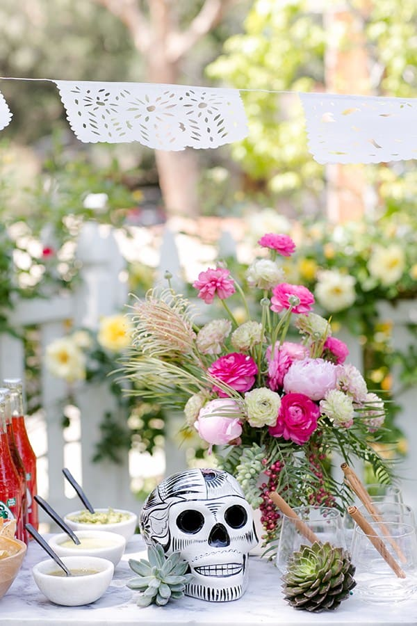 Pink flower arrangements with a black and white skull and salsa on a marble table outside for a Cinco de Mayo party.