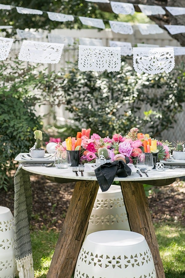 Cinco de Mayo table setting with pink flowers, fruit and benches.