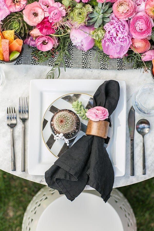 Cinco de Mayo table setting with black napkin, wooden napkin ring, pink flowers and black flatware.