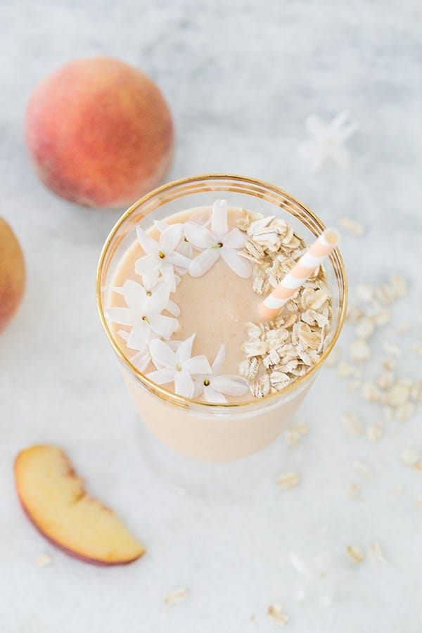Peach smoothie on a marble table garnished with fresh jasmine flowers and rolled oats.