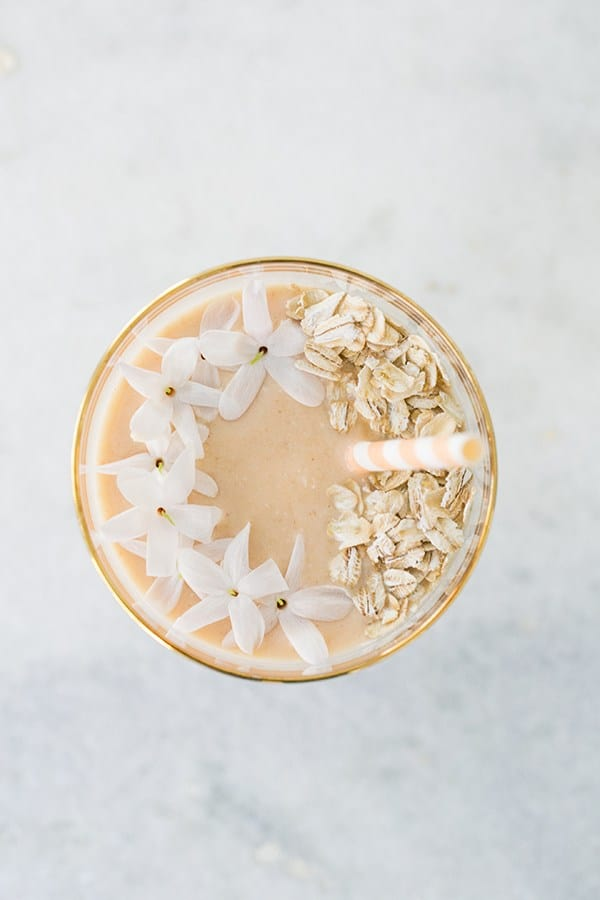 Peach smoothie with jasmine flowers, rolled oats and a paper straw