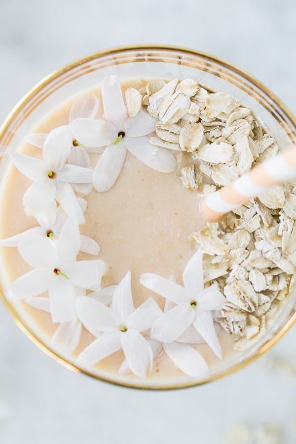 Close up picture of a smoothie with flowers and oats.