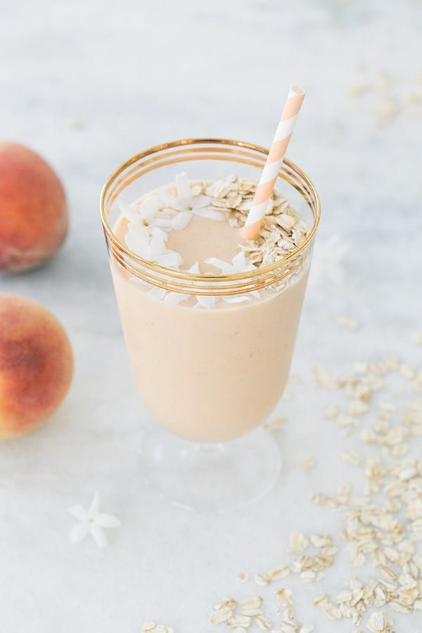 Peach smoothie with jasmine flowers, peach paper straw in gold glass.