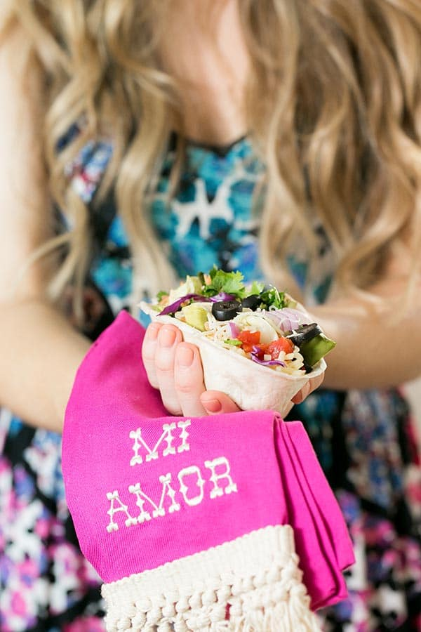 Girl holding a taco bowl filled with toppings.