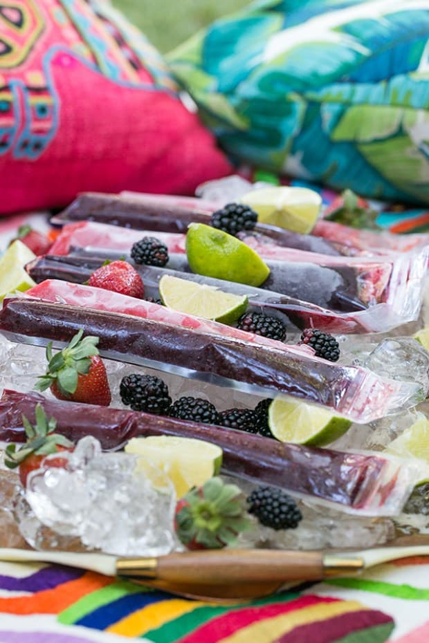 Frozen margarita popsicles on a tray with ice and lime wedges.