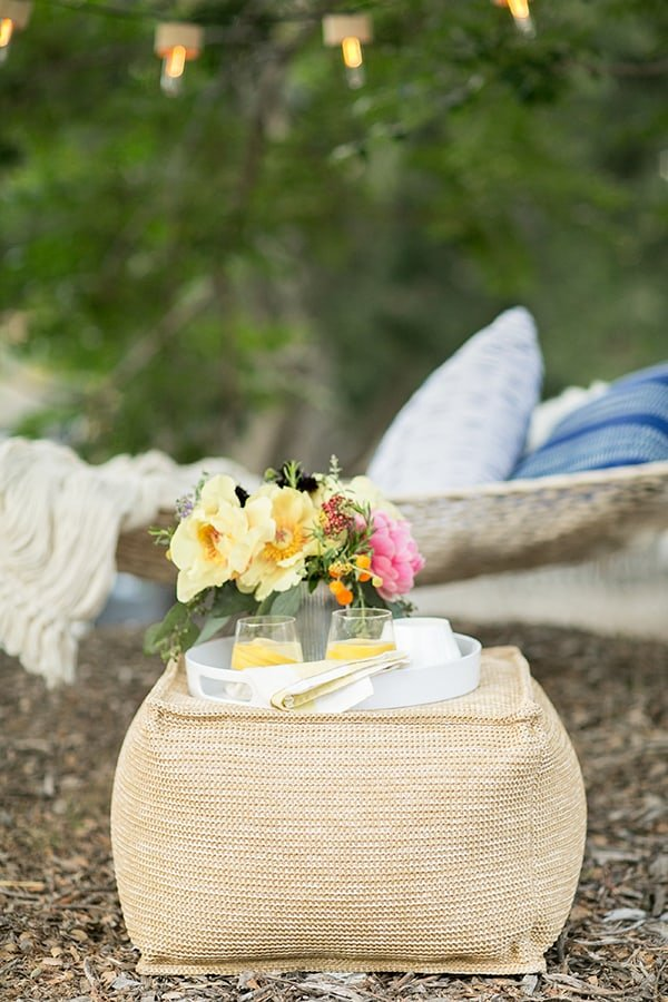 Outdoor pouf with a tray and flowers on it and a hammock in the back