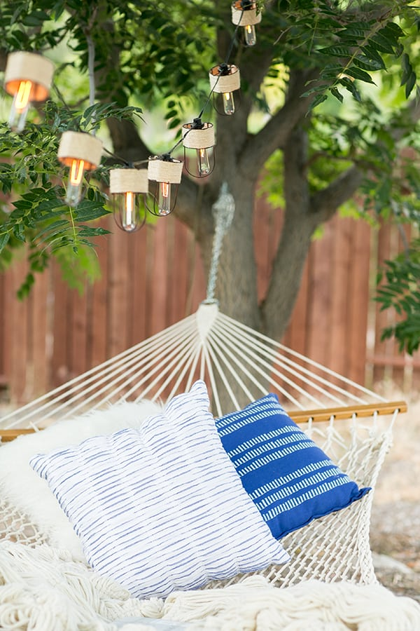 Hammock hung from a tree with three pillows and a blanket