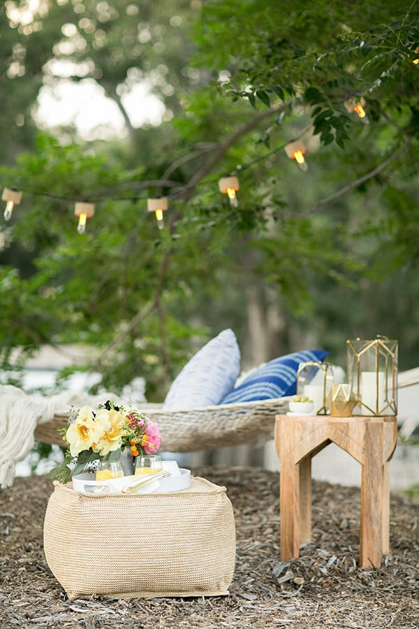 Outdoor hammock oasis with a pouf and a side table and outdoor lanterns
