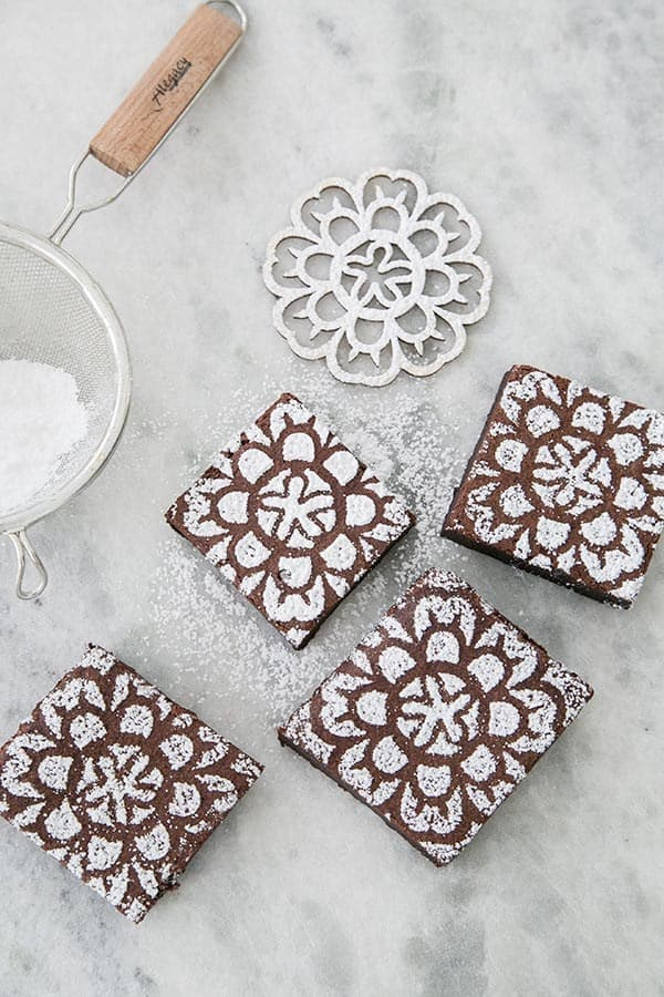 Chocolate brownies with a stencil and powdered sugar design.