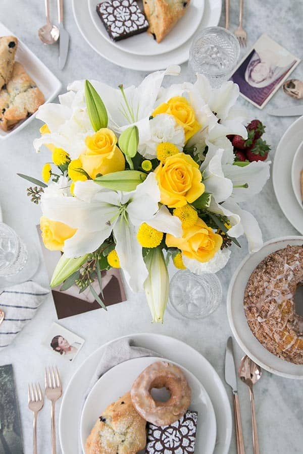 simple mother's day brunch with flowers, donuts, pictures on a marble table.