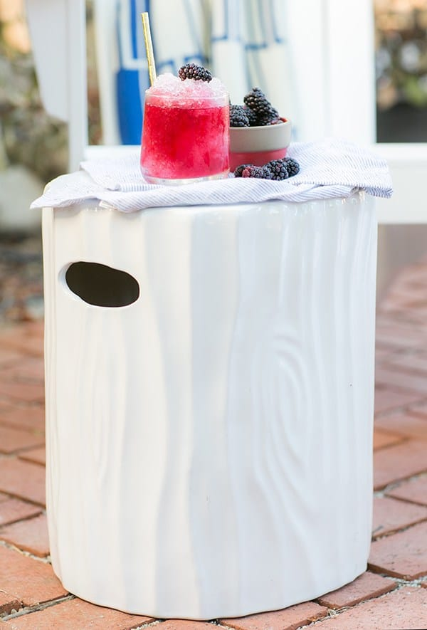 A white ceramic stool with a boozy snow cone and blackberries.