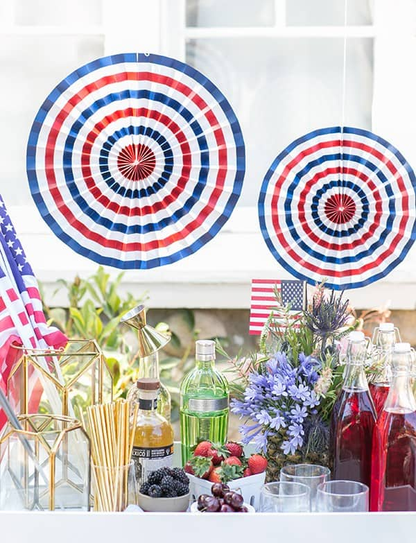 4th of July boozy snow cone stand with syrups, spirits, berries, paper fans and flowers.