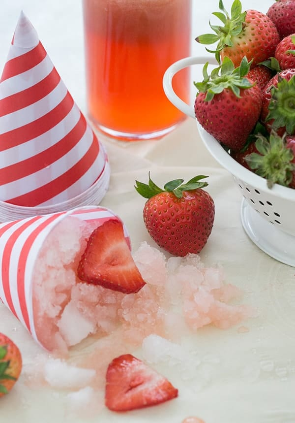 Strawberry snow cones with shaved ice, strawberries and snow cone syrup.