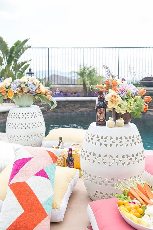 pool party ideas with pillows, flowers, drinks and garden stools.