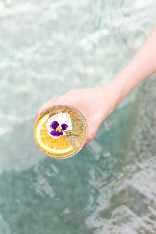 Hand holding a glass of pineapple party punch over a pool. It's garnished with an orange rind and edible flower.